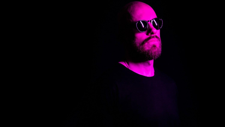 Bonkerin mainosalokuva, jossa on mies aurinkolasit päässä pinkissä valaistuksessa
