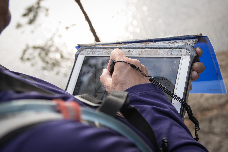 Henkilökuva Koopisteen Kimmo Viertolasta piirtämässä karttaa järvimaisemassa