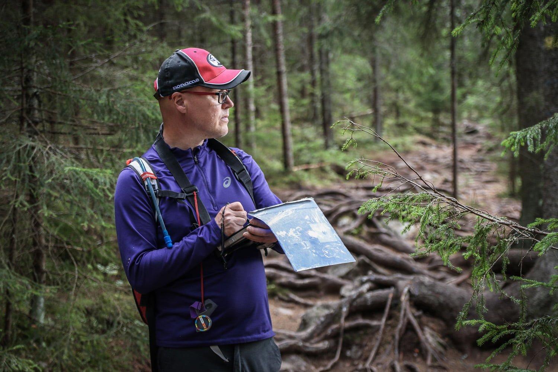 Henkilökuva Koopisteen Kimmo Viertolasta piirtämässä karttaa metsäpolulla