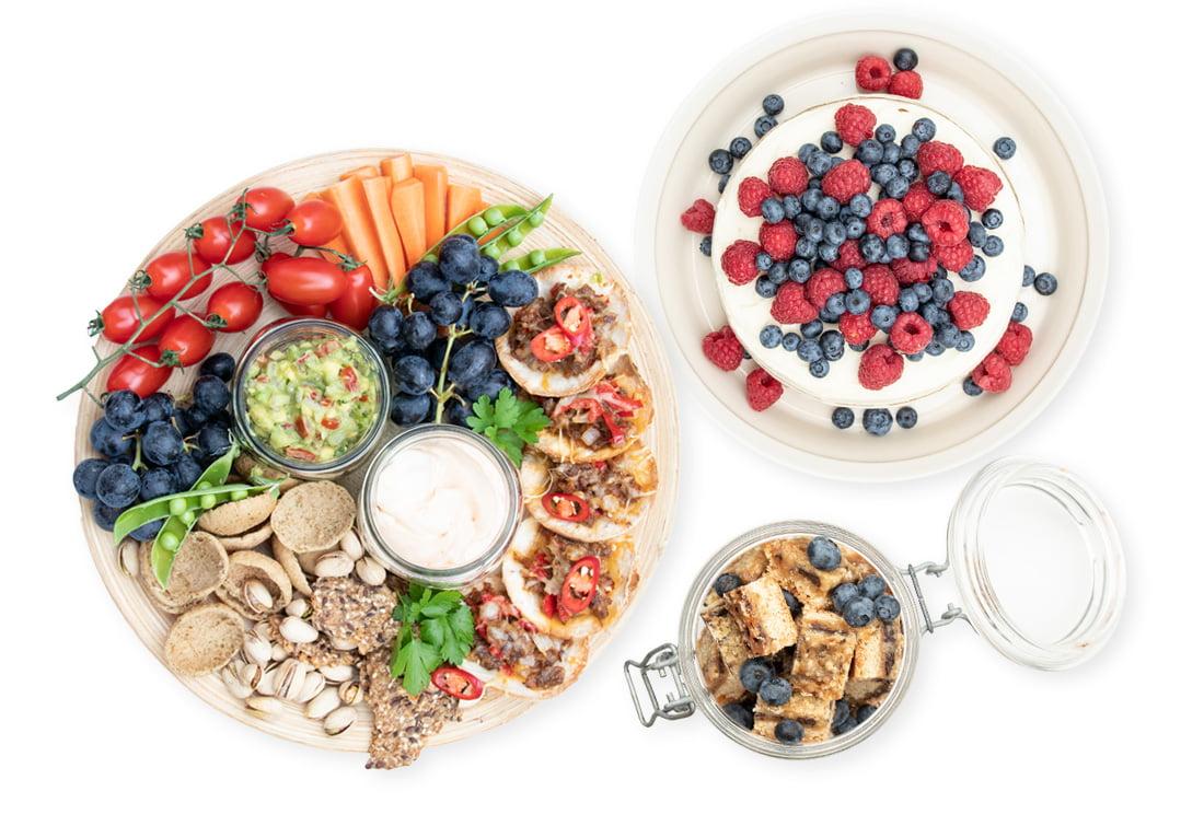 Kolme Vegeluokan annosta, illanistujaislankku, vadelma-mustikkakakku sekä carmelita-leivoksia, ylhäältä päin kuvattuna