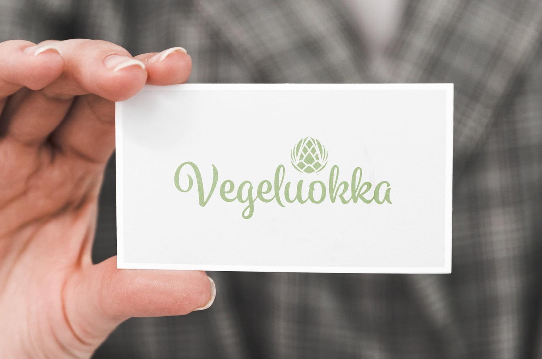 Käsi, joka pitää käyntikorttia, jossa on Vegeluokan logo