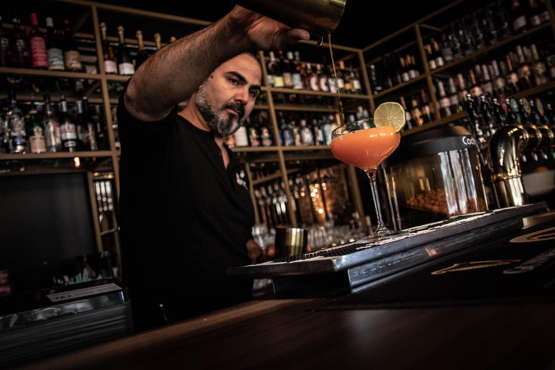 Henkilökuva Bar Prince Hamletista, jossa baarimikko kaataa cocktailia lasiin