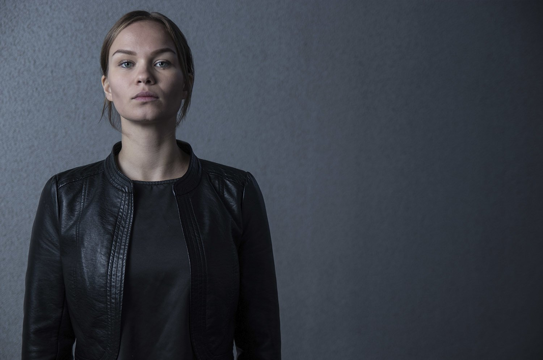 Henkilövalokuva, jossa nainen seisoo harmaan seinän edessä
