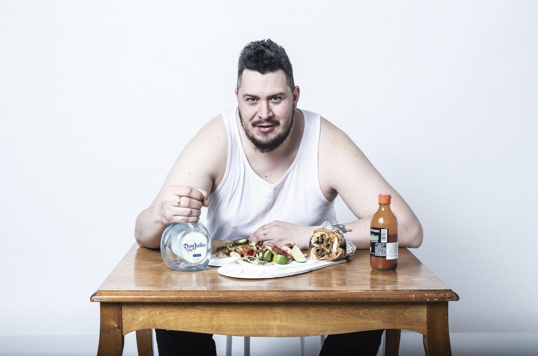 Henkilövalokuva, jossa mies istuu pullon ja tacoannoksen kanssa pöydän ääressä