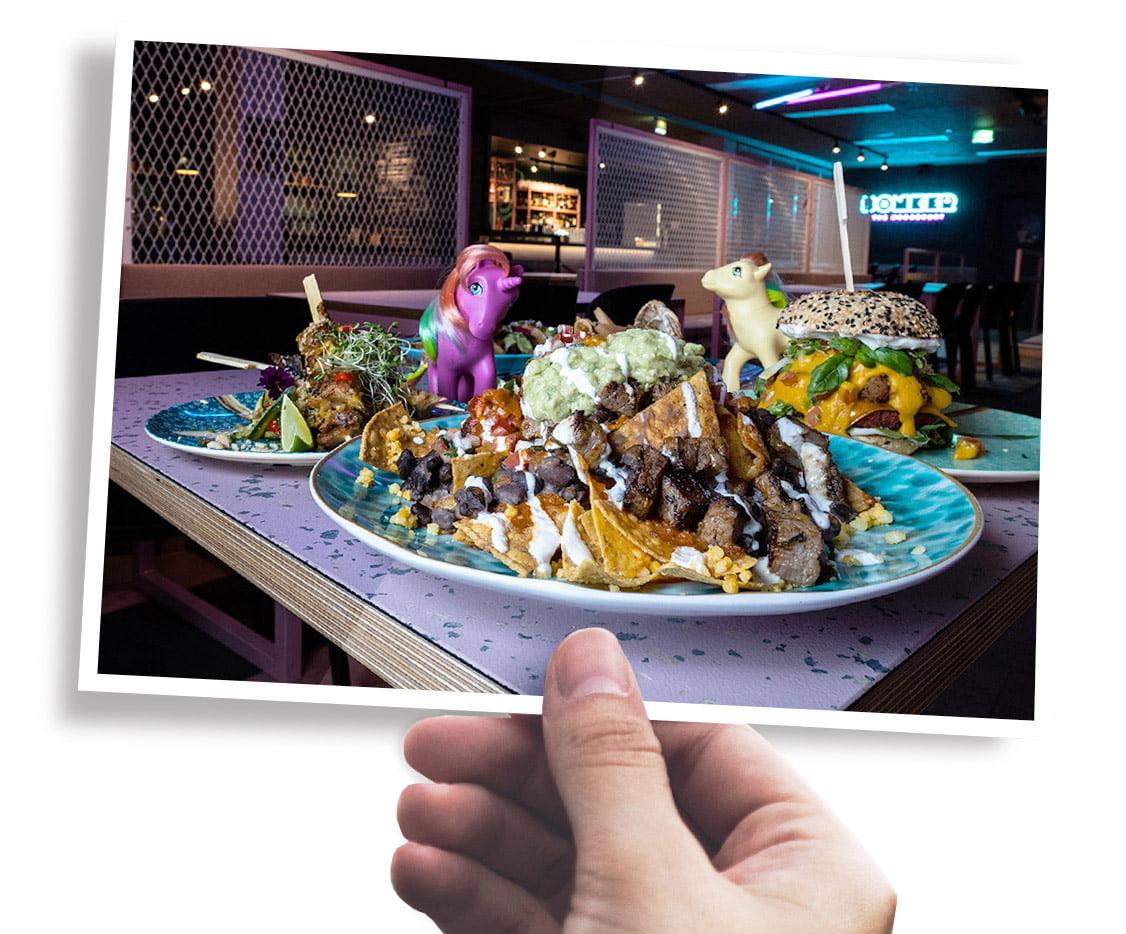 Käsi, joka pitelee tuotekuvaa HOAXin ja Tacos 'n' Tequilan ruoka-annoksista